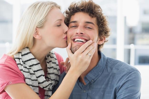 Kobieta całuje mężczyznę na jego policzku