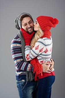 Kobieta całuje swojego chłopaka w policzek