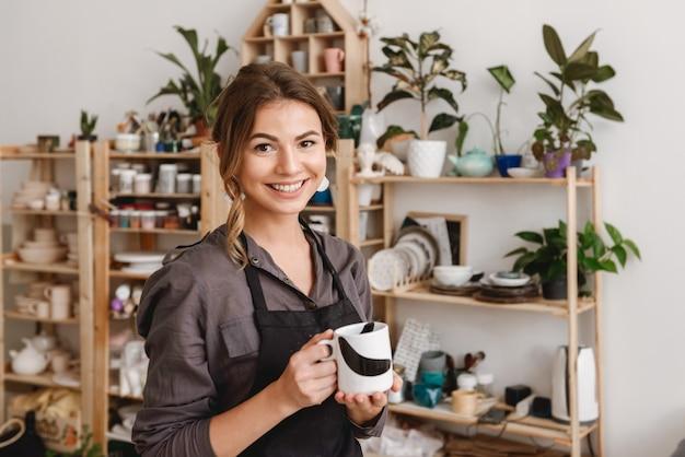 Kobieta ceramistka stojąca w studio ceramiki, trzymając kubek herbaty.