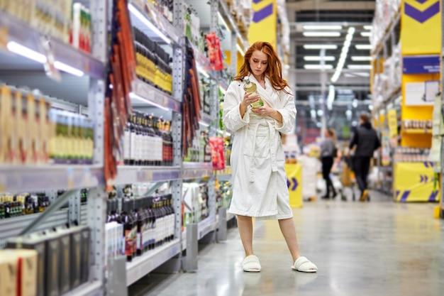 Kobieta chce kupić jakiś alkohol na weekendy, stoi w przejściu w supermarkecie, wybierając, w dziale alkoholi