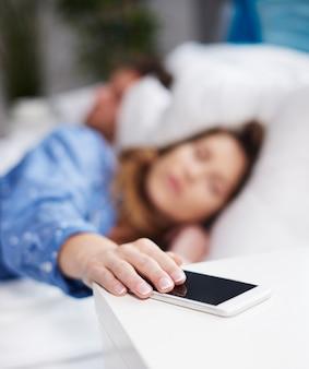 Kobieta chce wyłączyć budzik