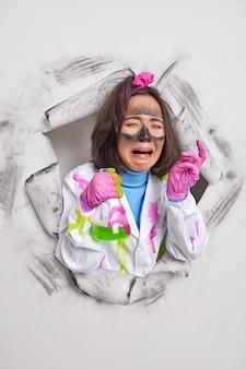 Kobieta chemik o ciemnych włosach trzyma butelkę z płynem chemicznym płacze z rozpaczy opracowuje lek przeciwwirusowy ubrana w biały fartuch ma brudną twarz pozuje przez dziurkę od papieru pracuje w laboratorium