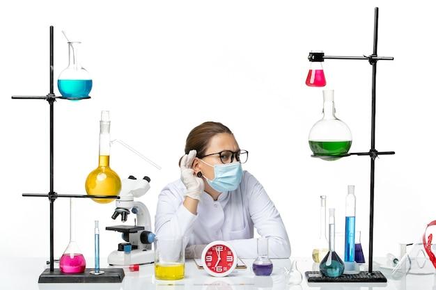 Kobieta Chemik W Garniturze Medycznym Z Maską Siedząca Z Roztworami I Próbująca Usłyszeć Na Białym Tle Plusk Chemii Wirusa Covid Lab Darmowe Zdjęcia