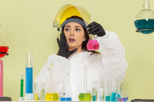 Kobieta chemik w specjalnym kombinezonie ochronnym pracująca z różnymi roztworami na jasnozielonej powierzchni