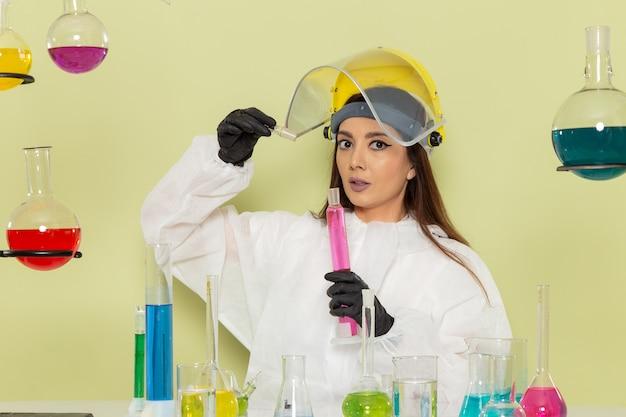 Kobieta chemik w specjalnym kombinezonie ochronnym pracująca z roztworami na zielonej powierzchni