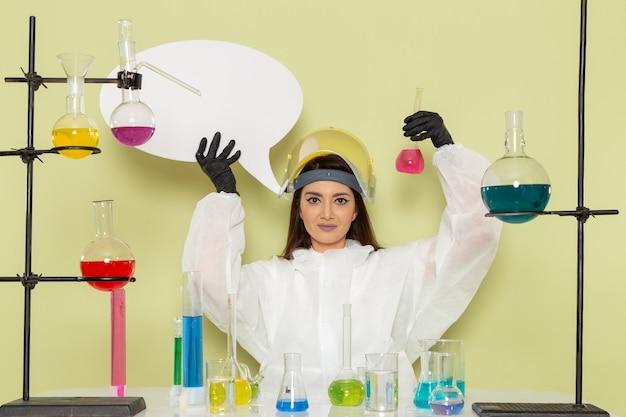 Kobieta chemik w specjalnym kombinezonie ochronnym z białym znakiem i roztworem na zielonej powierzchni