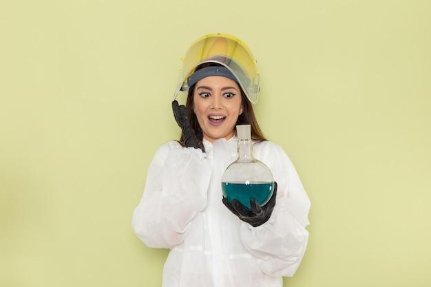 Kobieta chemik w specjalnym ubraniu ochronnym, trzymająca kolbę z roztworem na jasnozielonej powierzchni