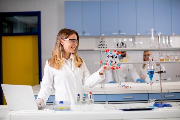 Kobieta chemik z okularami ochronnymi trzyma model molekularny w laboratorium
