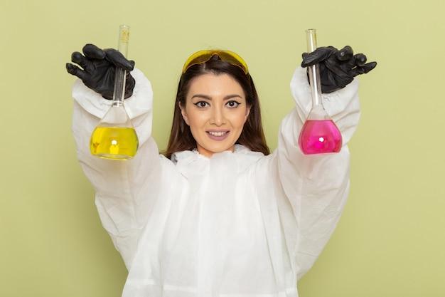Kobieta chemik z przodu w specjalnym kombinezonie ochronnym, trzymająca kolby z innym roztworem na zielonej powierzchni