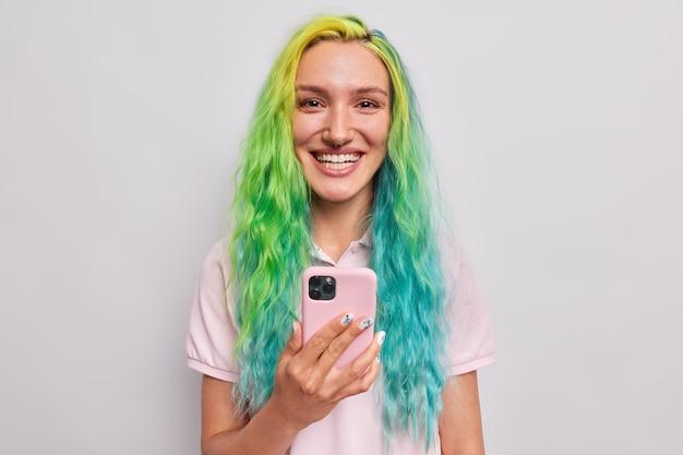 Kobieta chętnie pobrała aplikację na smartfona uśmiecha się szczęśliwie ma długie farbowane włosy przekłuwanie w nosie sukienki od niechcenia odizolowane na szaro