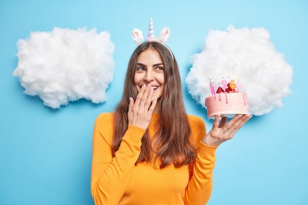 Kobieta chichocze radośnie przeciw usta ręką świętuje urodziny trzyma pyszne świąteczne ciasto nosi na co dzień pomarańczowy sweter jednorożec
