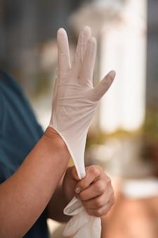 Kobieta chirurg lub pielęgniarka w sterylnym garniturze zakładającym sterylne gumowe rękawiczki do wykonania operacji,