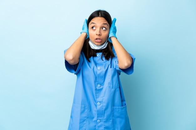 Kobieta chirurg nad niebieską ścianą sfrustrowany i obejmujące uszy