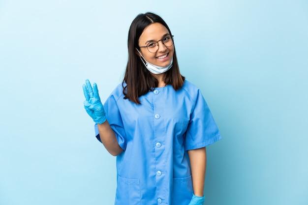 Kobieta chirurg nad niebieską ścianą szczęśliwy i licząc trzy z palcami