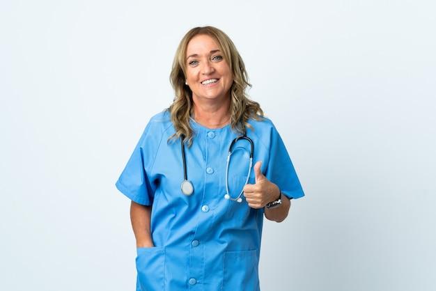 Kobieta chirurg w średnim wieku na białym tle, pokazując gest kciuka w górę