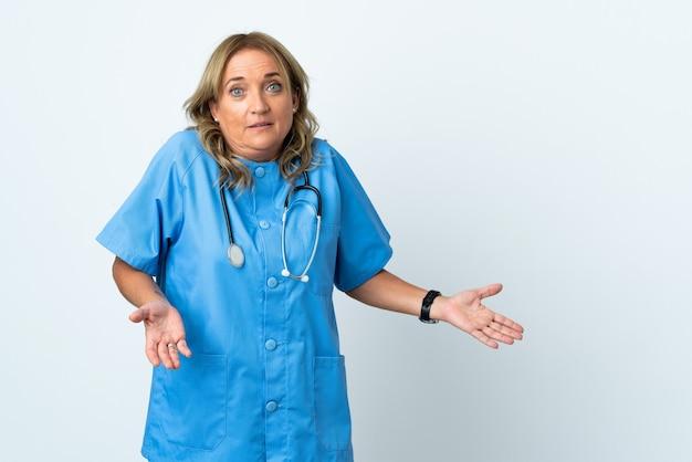 Kobieta chirurg w średnim wieku na odizolowanych z wyrazem zaskoczenia, patrząc z boku