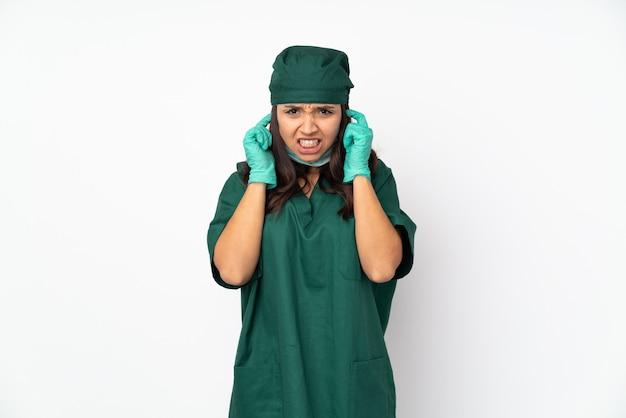 Kobieta chirurg w zielonym mundurze na białym tle sfrustrowany i obejmujące uszy