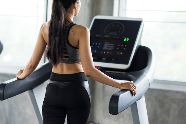 Kobieta chodzić i biegać na bieżni w siłowni