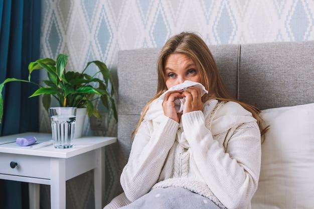 Kobieta chora na grypę w domu wydmuchuje nos trzymając chusteczkę, ma objawy przeziębienia lub grypy.