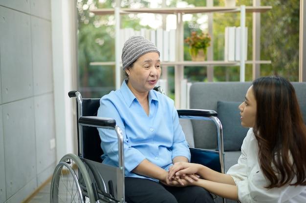 Kobieta chory na raka chusta na głowie siedzi na wózku inwalidzkim, mówi do jej wspierającej córki w pomieszczeniu, koncepcja zdrowia i ubezpieczenia.