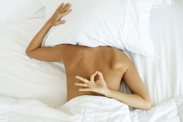 Kobieta chowa się pod poduszką i nie chce się obudzić