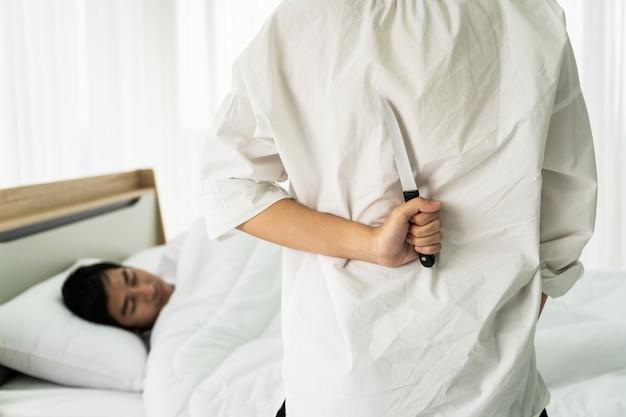 Kobieta chowa za sobą nóż i celuje w śpiącego na łóżku męża. pojęcie relacji niewiernej pary.