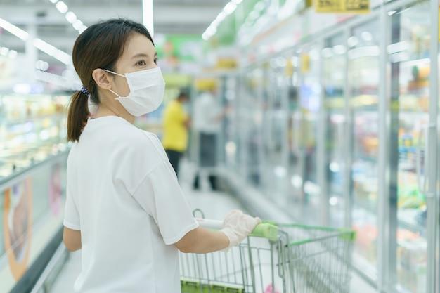 Kobieta chroni się przed infekcją maską chirurgiczną i rękawiczkami, z koszykiem na zakupy w supermarkecie po pandemii koronawirusa.