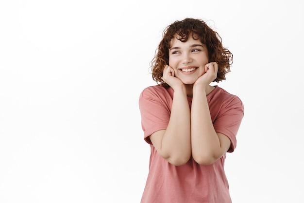 Kobieta, chuda twarz na rękach, podziwiaj coś z rozmarzonym uśmiechem stojąc w t-shircie na białym