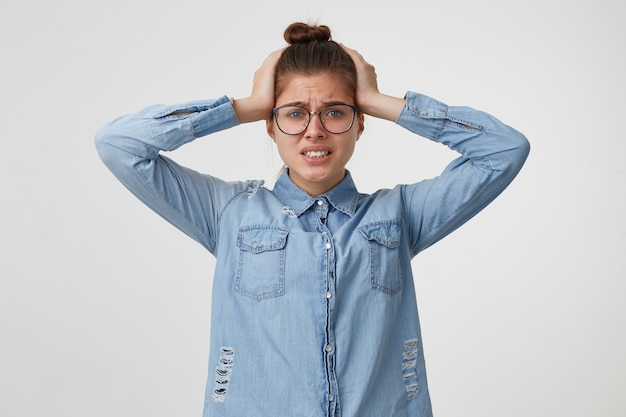 Kobieta chwyciła się za głowę w panice w rozpaczy, nie wie, gdzie biec ani co robić. o mój boże, katastrofa, zacisnęła zęby na białej ścianie.