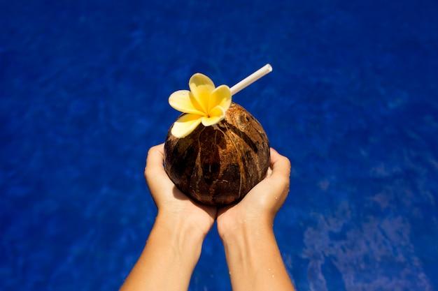 Kobieta chwyta napoju n kokosowe ręki przy basenem z błękitne wody tłem. styl instagram. letnie wakacje.