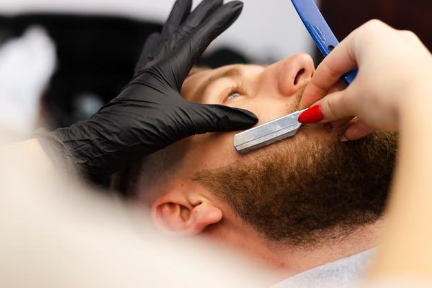 Kobieta cięcia brody klienta z bliska