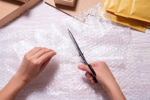 Kobieta cięcia folii bąbelkowej nożyczkami