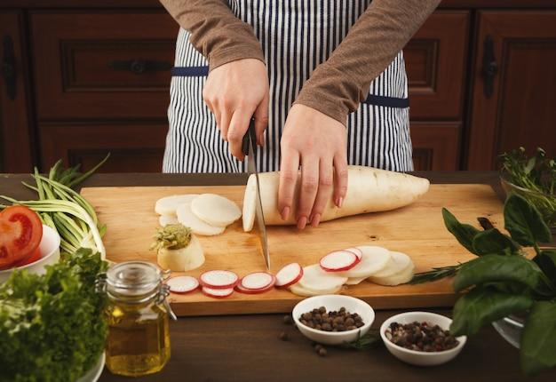 Kobieta cięcia świeżej rzepy na desce. naturalne odżywianie, przygotowywanie zdrowej dietetycznej sałatki warzywnej w kuchni, widok z boku