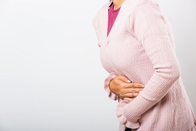 Kobieta cierpi na ból brzucha trzymając się za ręce na brzuchu