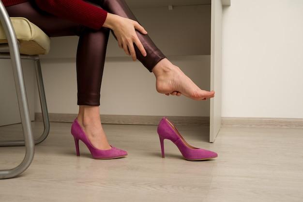 Kobieta cierpi na ból nóg w biurze. wytarła okropne zrogowacenia z niewygodnych butów na wysokim obcasie