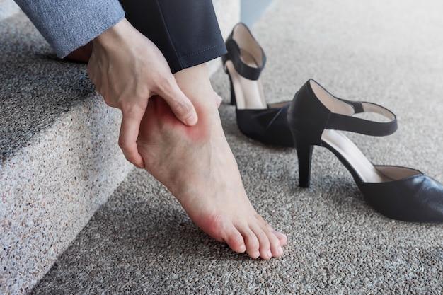 Kobieta cierpi na ból w kostce lub stopie