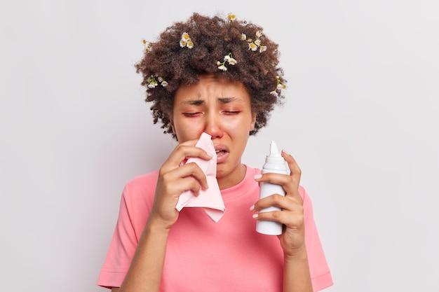 Kobieta cierpi na sezonową alergię wydmuchuje nos w serwetkę używa aerozolu ma problemy zdrowotne zaczerwienione oczy reaguje na alergen izolowany na białym