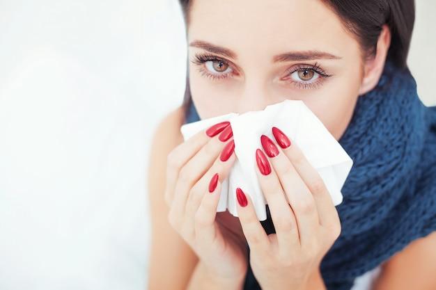 Kobieta cierpi na zimno leżąc w łóżku z tkanek