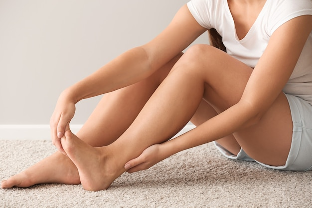 Kobieta cierpiąca na ból stopy podczas siedzenia na dywanie