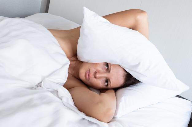 Kobieta cierpiąca na hałaśliwych sąsiadów zakrywa głowę poduszką. koncepcja stresu i złego snu