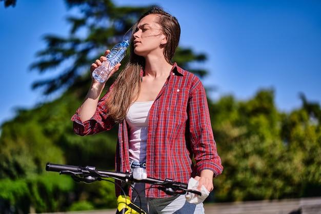 Kobieta cierpiąca na upał i pragnienie pije zimną orzeźwiającą wodę podczas jazdy na rowerze w parku w okresie letnim