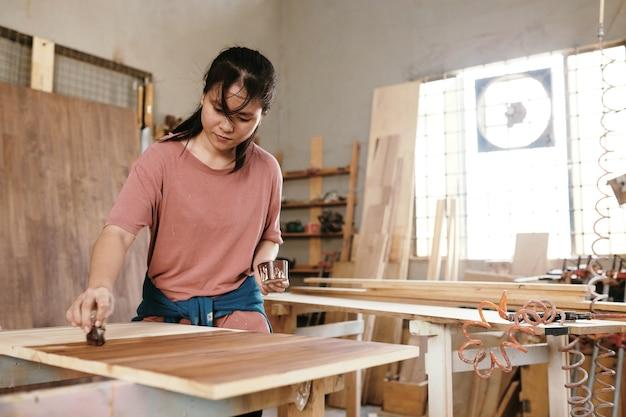 Kobieta cieśla lakierująca drewniana deska kawałek tkaniny nasączony płynnym roztworem