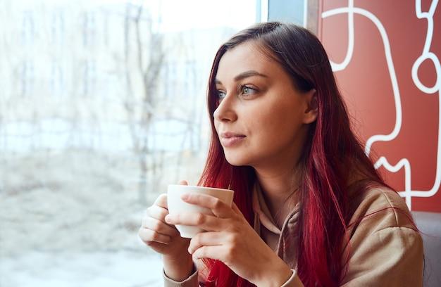 Kobieta, ciesząc się filiżanką kawy w kawiarni, patrząc przez okno