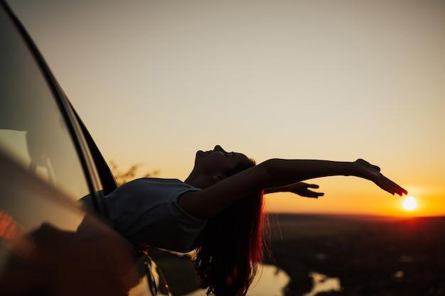 Kobieta, ciesząc się pięknym widokiem na zachód słońca latem, siedząc z podniesionymi rękami w samochodzie podczas zachodu słońca.