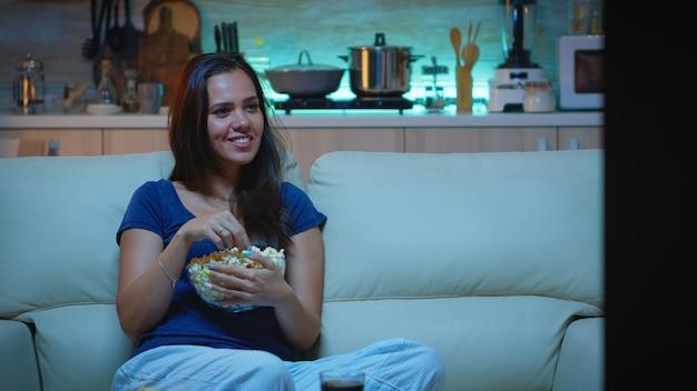Kobieta, ciesząc się wieczorem oglądając seriale w domu, siedząc na wygodnej kanapie, ubrana w piżamę. podekscytowana rozbawiona pani samotna w domu jedząca przekąski i pijąca sok na wygodnej kanapie w salonie.