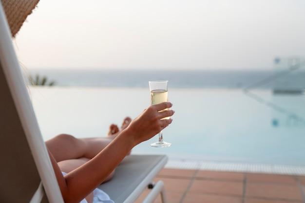Kobieta ciesząca się kieliszkiem białego wina przy basenie