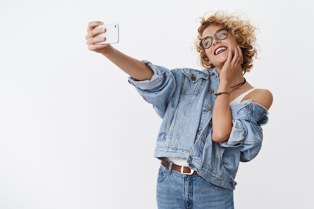 Kobieta ciesząca się robieniem selfie na nowym smartfonie, uwielbiająca aparat i idealne światło do dobrego zdjęcia pozuje śmiejąc się radośnie, radośnie wyciągając rękę z telefonem komórkowym, aby uzyskać kąt prosty nad białą ścianą