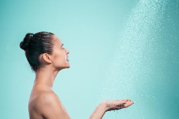 Kobieta ciesząca się wodą pod prysznicem pod strumieniem wody na niebieskim tle