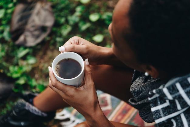 Kobieta cieszy się jej ranek kawę w naturze