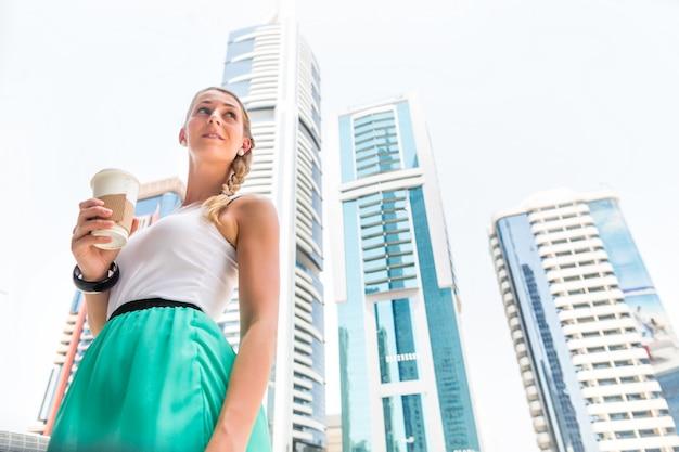 Kobieta cieszy się kawę iść w wielkomiejskim mieście